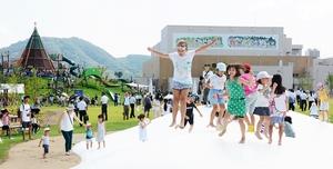 加古里子さんが監修しただるまちゃん広場で遊ぶ子どもたち。後方に壁画「越前山歌」を望む=2017年8月、福井県越前市高瀬2丁目