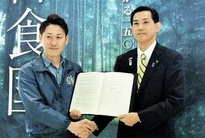 協定書を交わし握手する松崎市長(右)と鯖やの右田社長=3日、福井県小浜市食文化館