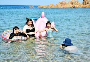 福井県美浜町のインバウンド観光PVビデオの撮影に挑む台湾人の女子大生3人=5日、同町の水晶浜海水浴場