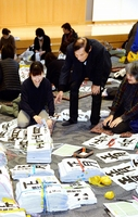 福井県かきぞめ競書大会の第1次審査で応募作品を見比べる審査員=1月13日、福井新聞社・風の森ホール