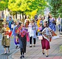 仏像をモチーフにしたメークと衣装でまちを歩く参加者=15日、福井市大手3丁目