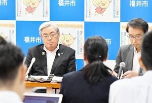 大勢の記者の質問に聞き入る東村新一市長(左奥)=6月1日、福井県福井市役所