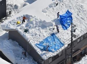 天候が安定している間に屋根雪下ろしする人たち=9日、福井県勝山市内