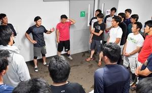 選手を集め、雨天中止を伝える田中雅彦監督(中央左)=富山県の高岡西部総合公園野球場