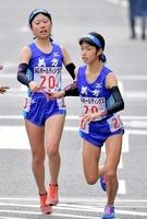 女子美方の1区橋本はなえ(左)からたすきを受け取る2区藤井結愛=京都市内の第1中継所