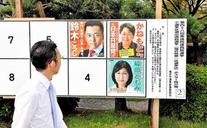 選挙ポスターを眺める若者。何を基準に一票を投じる?=11日、福井市大手3丁目