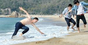 気温が25度を超える夏日となった福井県美浜町。ダイヤ浜海水浴場では、薄着の男性が水際で気持ちよさそうにはしゃいでいた=16日午後2時20分ごろ