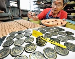 越前がに漁の解禁を前に、次々と作られる越前焼の「極」タグ=6日、福井県越前町樫津の国成窯