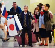 成田空港に到着したヒラヌマ・ニコライさん(中央)=18日午後