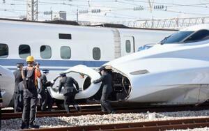 山陽新幹線の復旧訓練で、救援用列車とつなぐために先頭車両のボンネットを外す車掌ら=30日午後、福岡県那珂川市