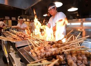 炭火で鳥を焼き上げる店員=福井市順化2丁目の秋吉福井片町店