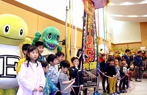 通算入館者数が1千万人を突破し、くす玉を割って喜ぶ子どもたち=3月31日、福井県勝山市の県立恐竜博物館