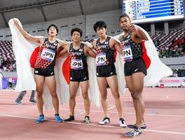 男子1600メートルリレーで優勝し、日の丸を背にポーズをとる(右から)ウォルシュ、佐藤、伊東、若林の日本チーム=ドーハ(共同)