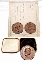 見つかったウィーン万博「進歩賞牌」のメダル(下)。メダルの形状の紙が貼り付けられた賞状(上)とセットとみられる