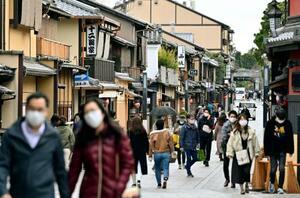 京都・祇園をマスク姿で歩く人たち=28日午後