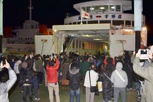 宇野港に到着した「宇高航路」の最終便となるフェリーを出迎える大勢の人たち=15日夜、岡山県玉野市