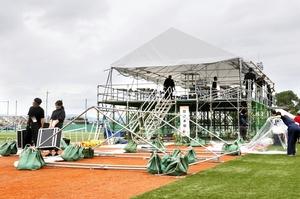台風接近に備え、福井国体サッカー競技本部のテントの幕を外し機材を運び出す関係者=9月30日、福井県坂井市丸岡スポーツランド