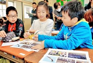 記事の内容に合った写真について話し合う児童たち=17日、福井市の松本小